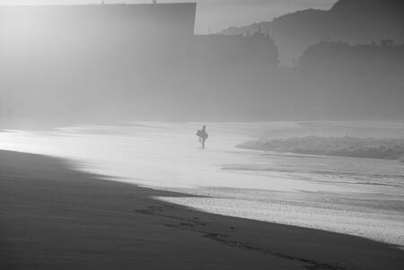 Bodyboarder at sunset in black and white