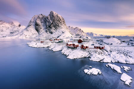 Fishermen's huts in the snowy mountain peak of Hamnoy