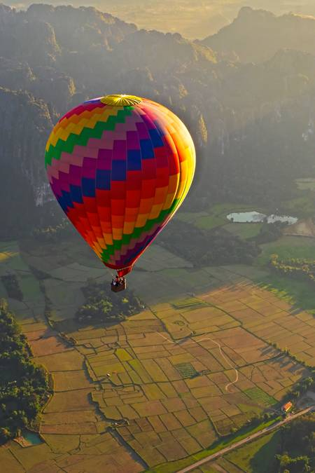 Hot air balloon over rice paddies