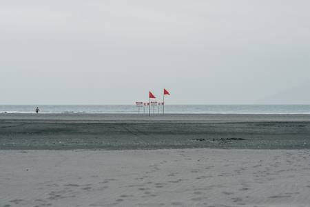 Red flags and black sand