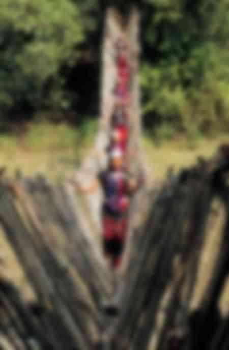 Wa Frauen überqueren eine Bambusbrücke