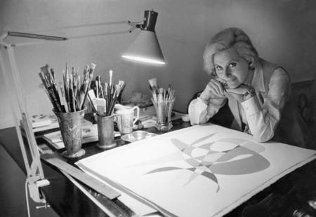 Michèle Morgan sitting at her drawing table