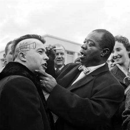 Le Jazzman Américain Louis Armstrong signant un autographe