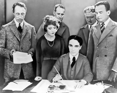 Charlie Chaplin signant un contrat cinématographique