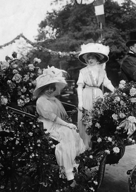 Jeunes femmes élégantes assises dans une calèche décorée pour la Fête des fleurs