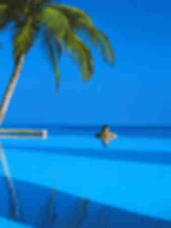 Woman in swimming pool looking at sea Maldives