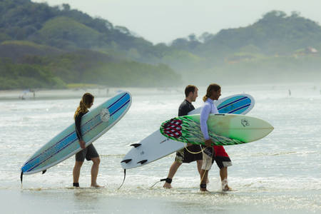 Coppia andando a lezione di surf sulla spiaggia di Playa Guiones