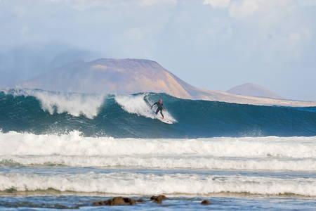Surfista su una grande onda con oltre l'isola Graciosa