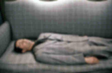 Pierre Mortez vêtu d'un costume à carreaux gris assorti à son canapé