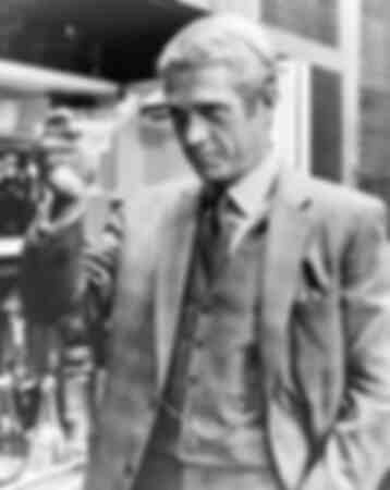 Steve McQueen raising a glass of wine