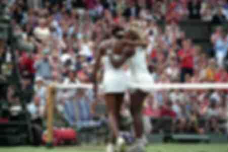 Les soeurs Serena et Venus Williams des Etats-Unis s'embrassent au-dessus du filet après la finale de Wimbledon