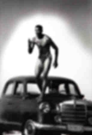 Iván Pedroso pose sur le capot d'une Mercedes à La Havane 2000